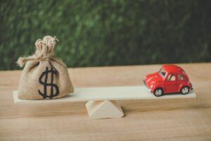 red miniature car and money bag with dollar sign balancing on seesaw on green background