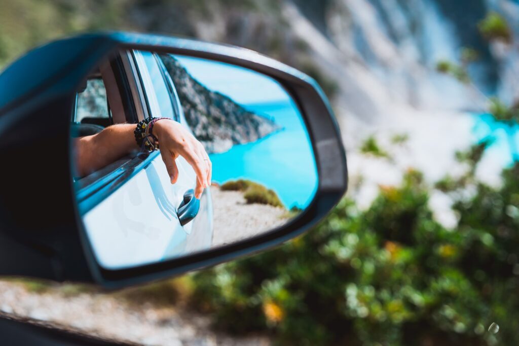Female hand mirrored in the car side view mirror., after summer car service. Blue mediterranean sea and white rocks in