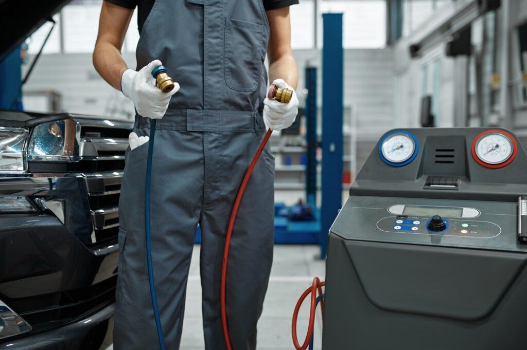Male mechanic refills air condition, car service